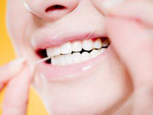 femme passant le fil dentaire - concept soins dentaires